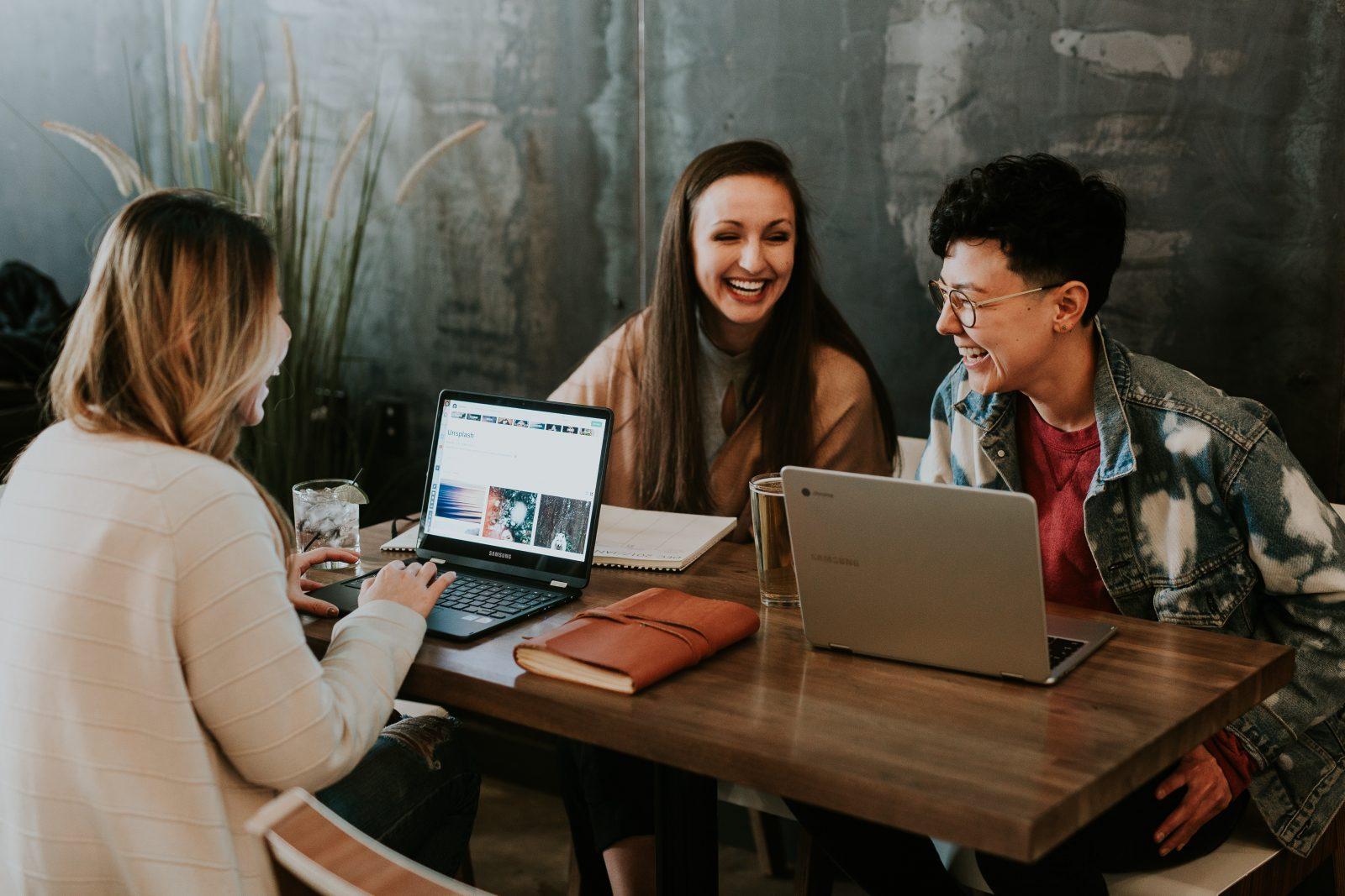 kolme opiskelijaa istuu pöydän ääressä ja nauraa