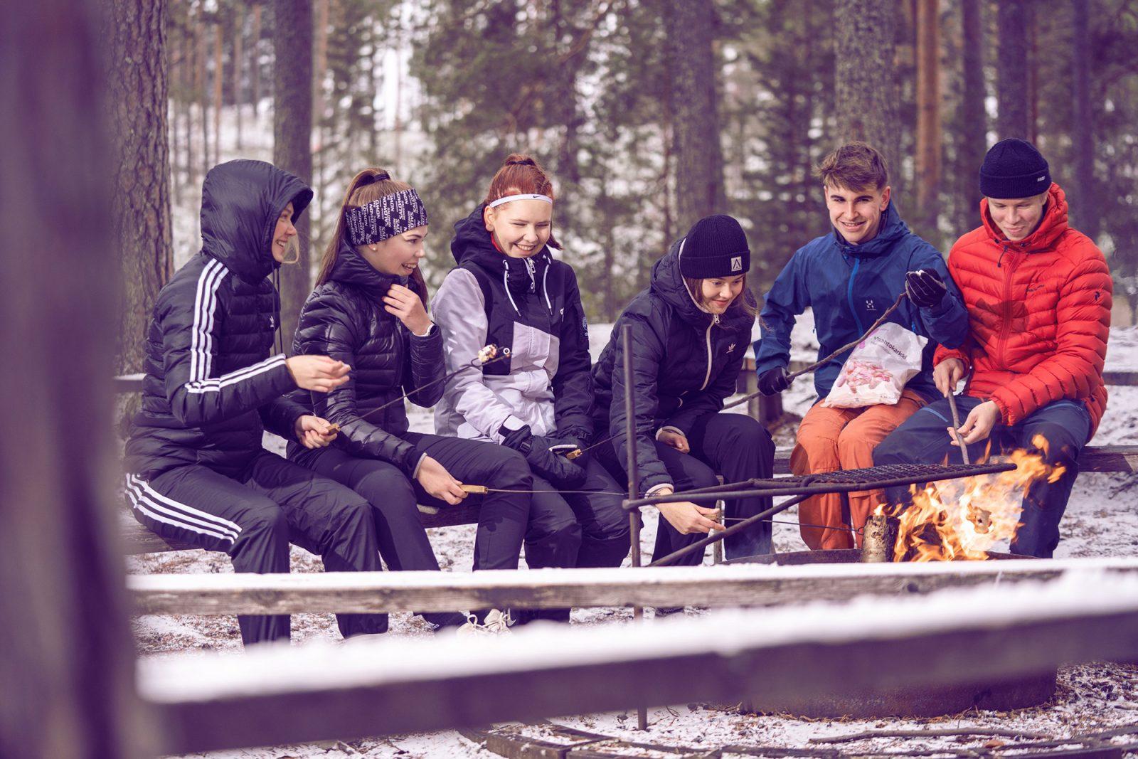Nuoret istuvat nuotiopaikalla ja paistavat vaahtokarkkeja