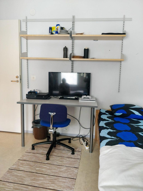 kuva solun huoneesta, jossa on sänky ja työpöydällä pelikonsoli