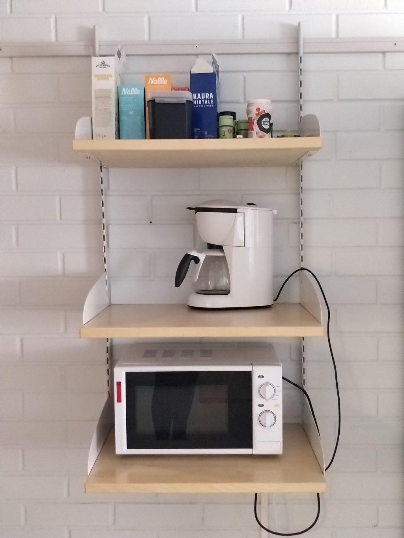 solun keittiön hyllykkö, jossa kuivaelintarvikkeita, kahvinkeitin ja mikroaaltouuni