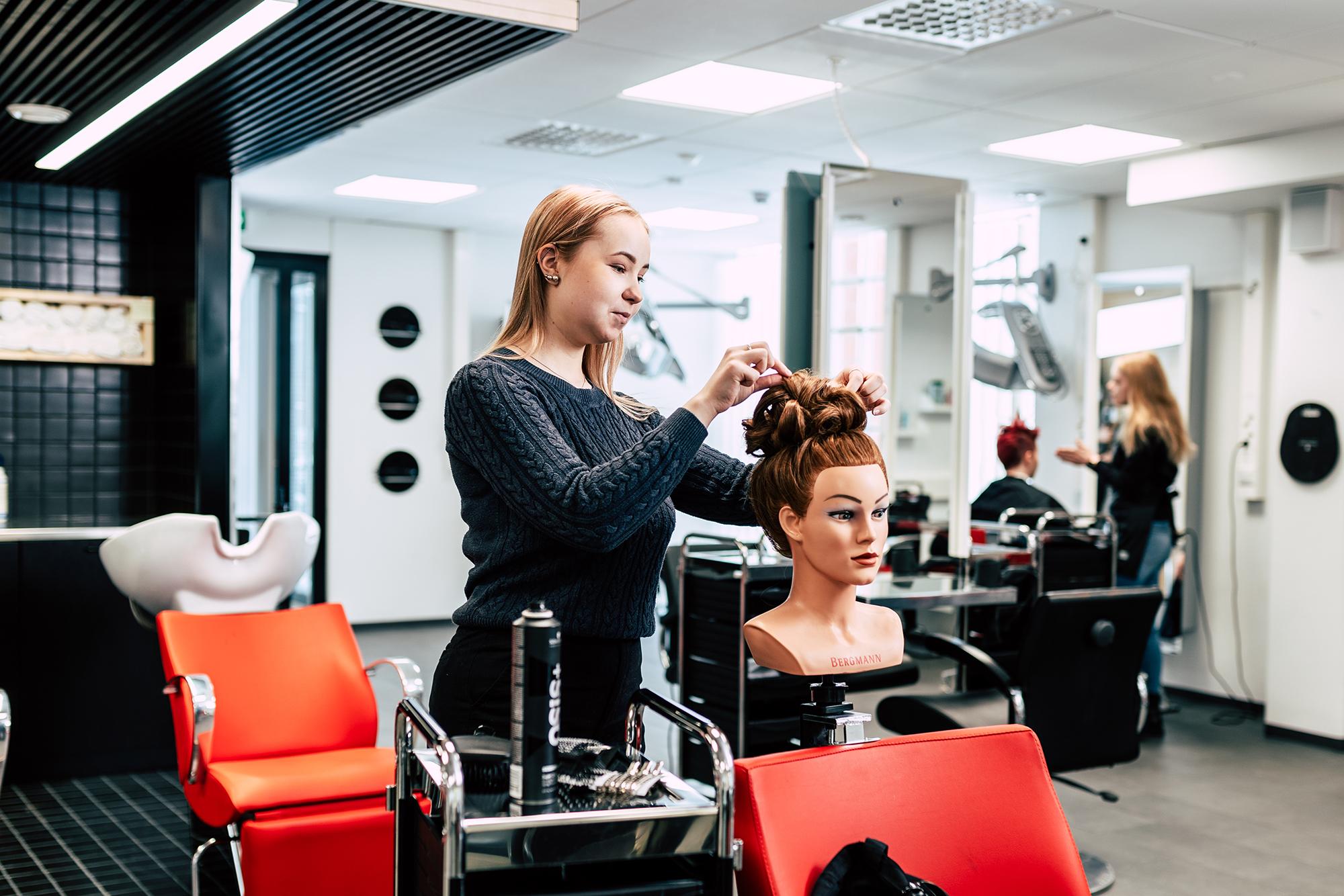 Kampaaja laittaa kampauspään hiuksia