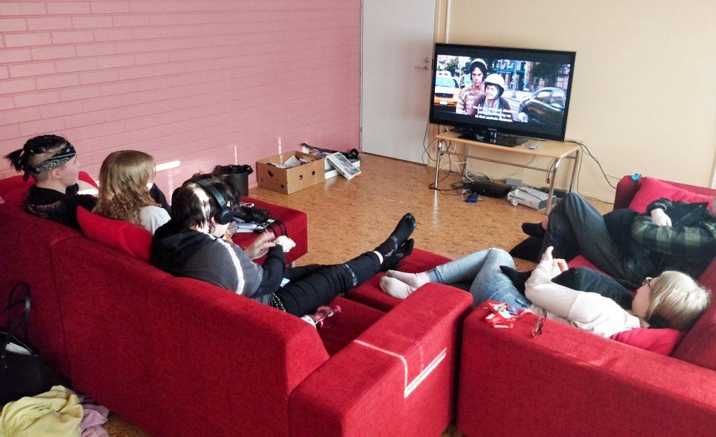 te-huoneen sohvilla makaa tyttöjä katselemassa televisiota