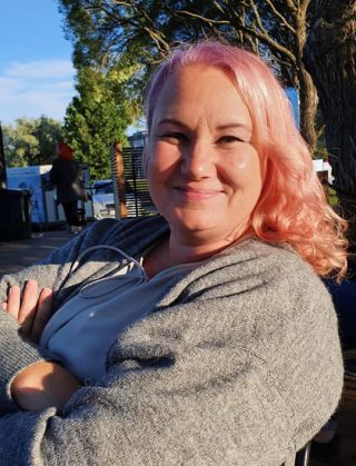 Nainen, vaaleanpunaiset hiukset katsoo kohti kädet ristissä.