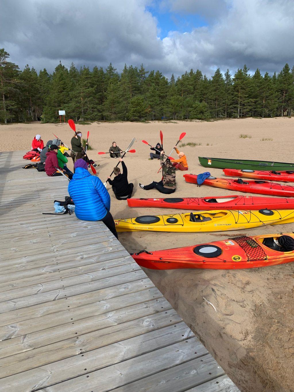 Ihmiset istuvat hiekalla ja harjoittelevat melomista, kanootit vieressä.